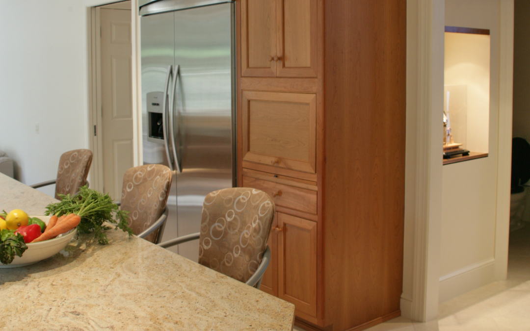 The microwave is concealed in cabinetry adjacent to the fridge