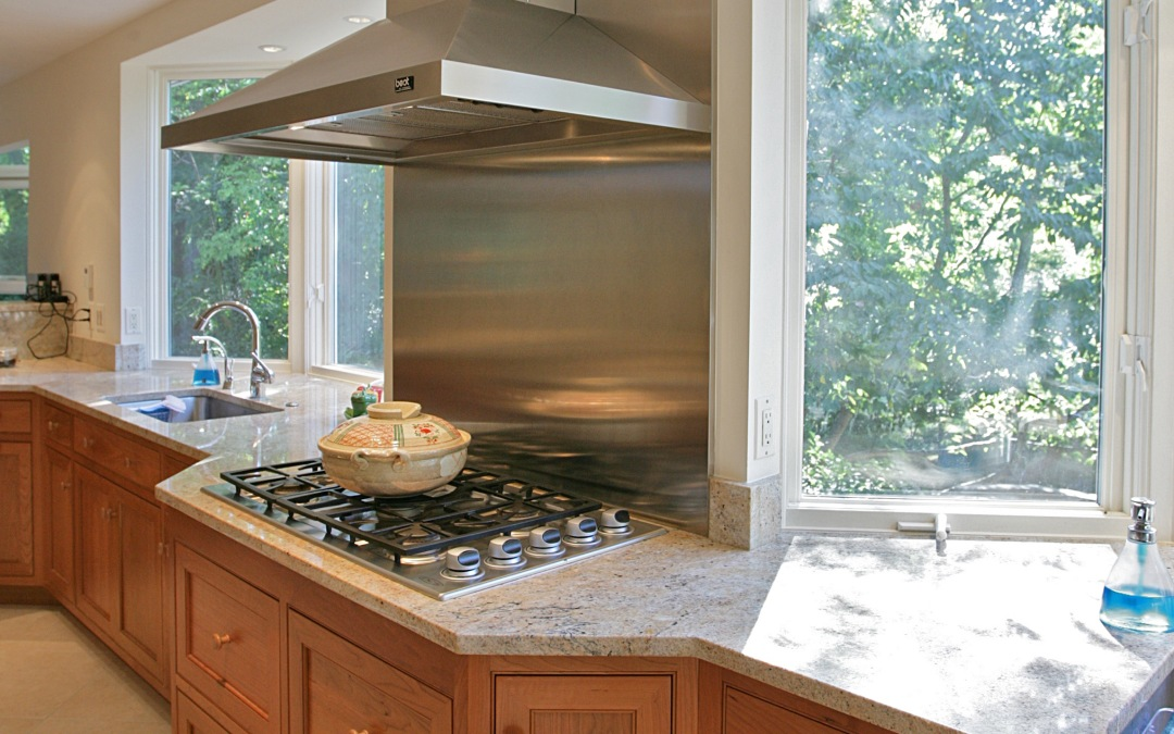 The gas cooktop and stainless steel backsplash