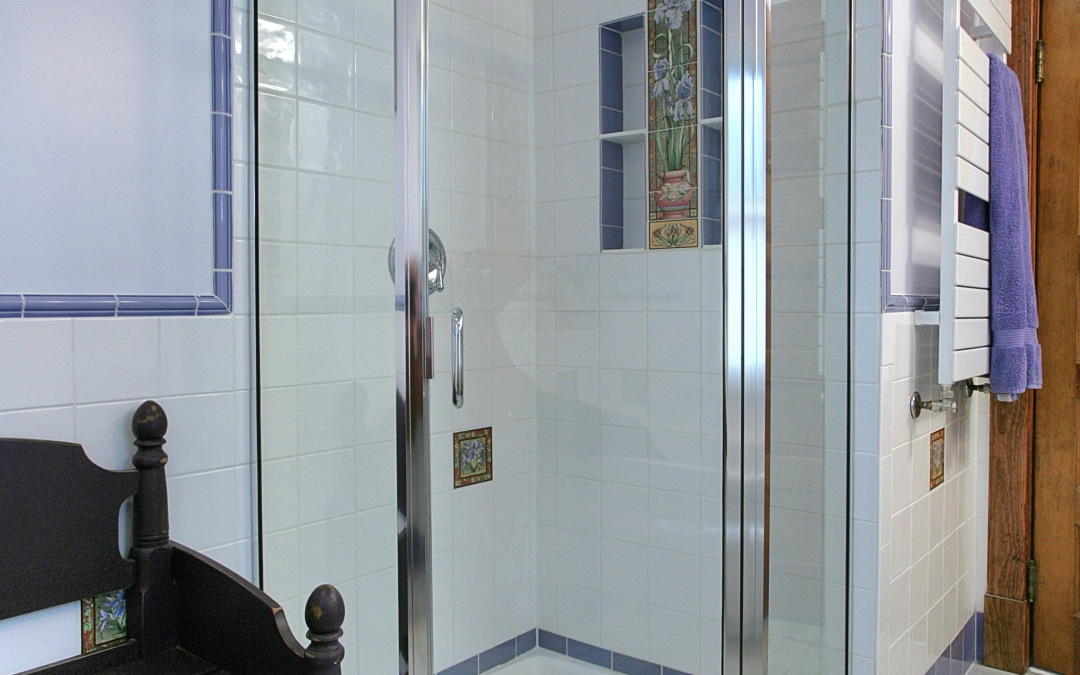 A neo-angle shower, tiled niches, and towel warmer